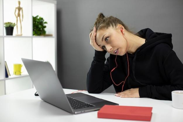 Zmęczony zdziwiony freelancer pracuje przy laptopie, trzyma rękę na czole, wypalenie zawodowe