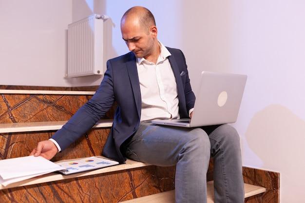 Zmęczony zestresowany biznesmen traci koncentrację na biznesowym terminie w miejscu pracy. przedsiębiorca korporacyjny za pomocą laptopa robi w godzinach nadliczbowych, siedząc na klatce schodowej.