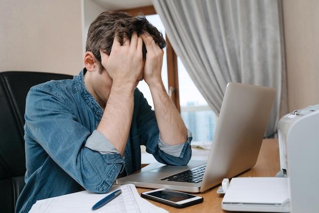 Zmęczony zestresowany młody mężczyzna siedzący przed laptopem, sfrustrowany