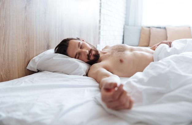 Zmęczony zmęczony młody człowiek, leżąc i śpiąc w łóżku