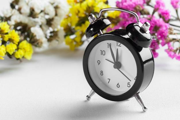 Zmiana czasu wiosennego z budzikiem i gałęziami kwiatów