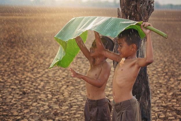 Zmiana klimatu azjatyccy chłopcy cieszą się pierwszą porą deszczową na suchym popękanym gruncie ochrona środowiska i powstrzymanie koncepcji globalnego ocieplenia
