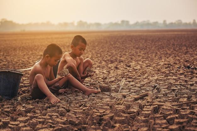Zmiana klimatu dwóch azjatyckich chłopców spacerujących i poszukujących wody na suchej ziemi i zachodzie słońca ochrona środowiska i powstrzymanie koncepcji globalnego ocieplenia