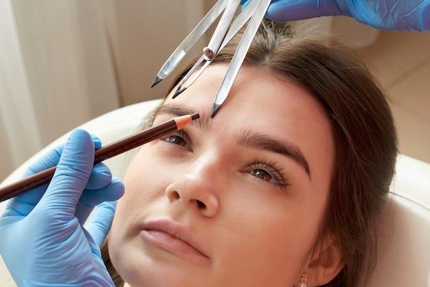 Zmiana kształtu brwi. stylistka mierząca brwi linijką. przebieg pracy mikropigmentacyjnej w gabinecie kosmetycznym. kobieta o brwiach podbarwionych półtrwałym makijażem.