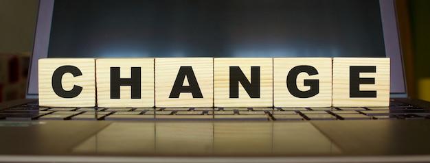 Zmiana słowa. drewniane kostki z literami na klawiaturze laptopa. pomysł na biznes.