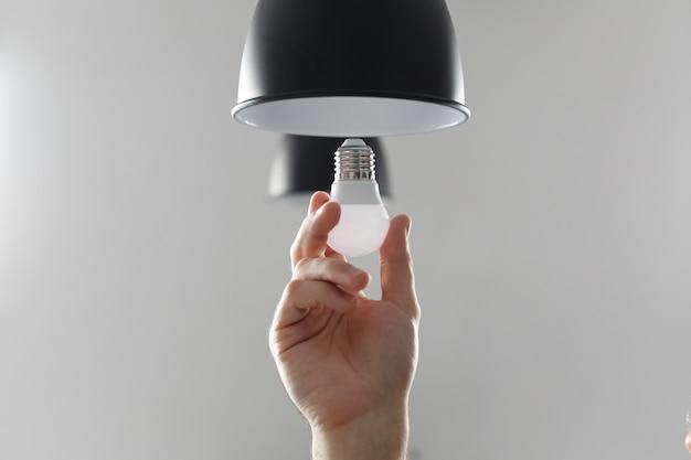 Zmiana żarówki na żarówkę led w lampie podłogowej w kolorze czarnym. na jasnoszarym tle
