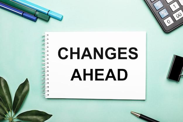 Zmiany nadchodzące jest napisane na białej kartce na niebieskiej powierzchni w pobliżu papeterii i arkusza schefflera. motywacyjna koncepcja.