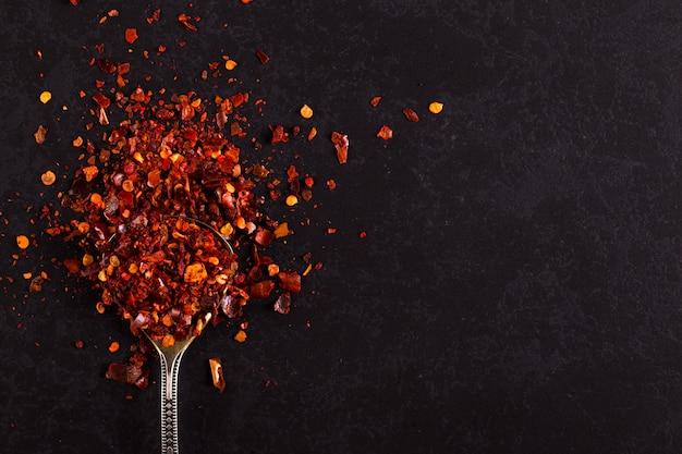 Zmiażdżone suszone papryczki chili w żelaznej łyżce porozrzucanej na czerni. , copyspace.