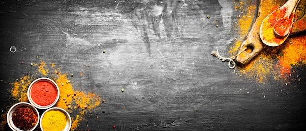 Zmielone kolorowe indyjskie przyprawy i zioła. na czarnej tablicy.