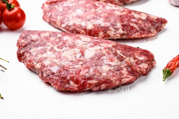 Zmielone paszteciki z surowego mięsa. kotlet mięsny gotowy do gotowania. zestaw ekologicznego mięsa z farmy, na białym tle kamiennego stołu