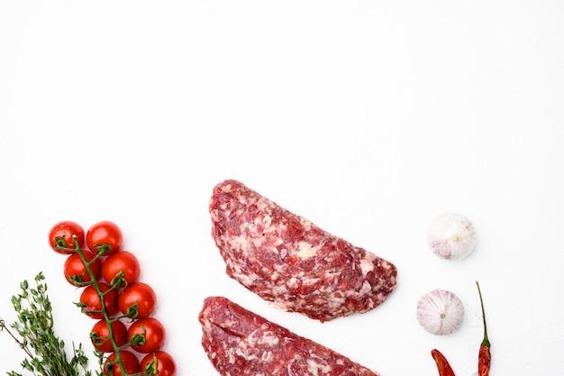 Zmielone paszteciki z surowego mięsa. zestaw pasztecików mięsnych, na białym tle kamiennego stołu, płaski widok z góry, z miejscem na kopię tekstu