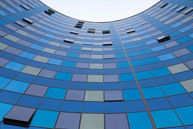Zmielony widok błękitna szkło powierzchnia buduje frontową ścianę półkole odbija niebieskie niebo
