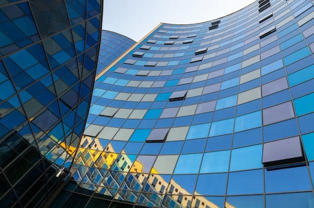Zmielony widok niebieska szklana powierzchnia półkola budynku ściana odbija niebieskie niebo z okno błękitni i złoci kolory