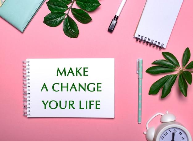 Zmień zmianę swoje życie jest napisane na zielono na białym notatniku na różowej powierzchni otoczonej notatnikami, długopisami, białym budzikiem i zielonymi liśćmi