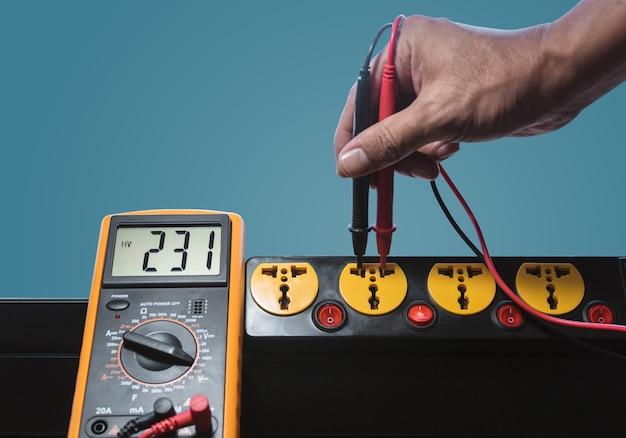 Zmierz napięcie ac 230 v z gniazdka elektrycznego miernikiem cyfrowym.