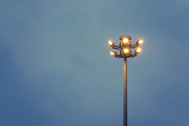 Zmierzch i wysoki maszt z powodzi światłami przy parkiem sportowym