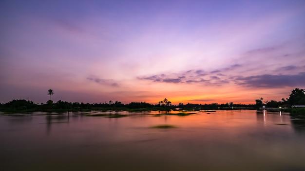 Zmierzch krajobraz nad rzeką i sylwetka drzewa z długimi ekspozycjami nakręcony w tajlandii