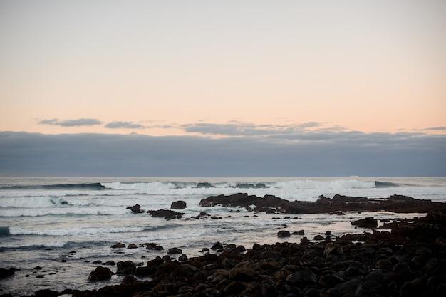 Zmierzch nad falującym wybrzeżem morskim z dzikimi kamieniami w wietrzny wieczór pod niebem
