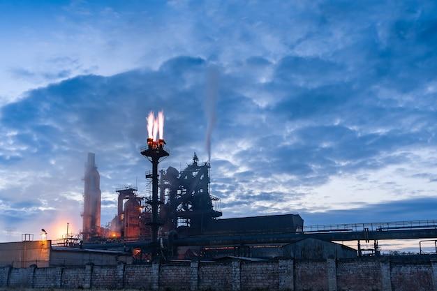 Zmierzch pejzaż zakładu chemicznego z rurami i dymem, światłami i dymem, długa ekspozycja