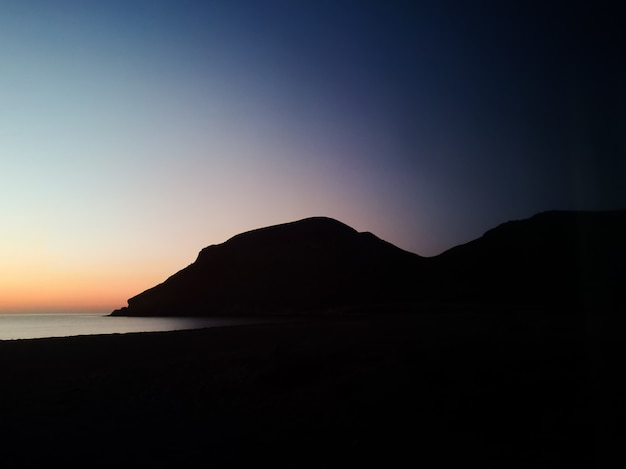 Zmierzch z sylwetki górą na plaży