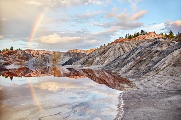 Zmierzch z tęczą w piasków wzgórzach. bajkowy magiczny krajobraz. piękne kolorowe góry, jeziorny kolor czerwony