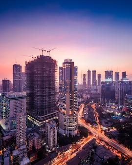 Zmierzchowy widok na panoramę bombaju w fioletowych odcieniach, pokazujący wiele drapaczy chmur i wieżowców w budowie oraz mieszkalnych i komercyjnych