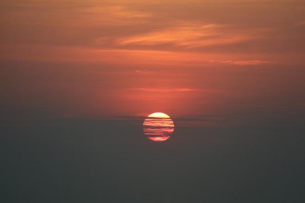 Zmierzchu z powrotem onsilhouette nieba wieczór czerwona pomarańczowa chmura i ciemne niebo nad horyzontu morzem