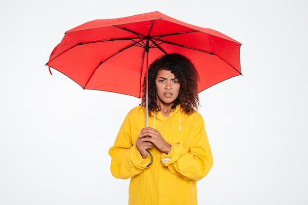 Zmieszana afrykańska kobieta w płaszczu chuje pod parasolem