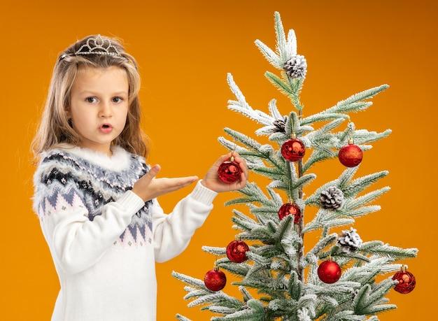 Zmieszana dziewczynka stojąca w pobliżu choinki ubrana w tiarę z girlandą na szyi i wskazuje na bombkę na białym tle na pomarańczowym tle