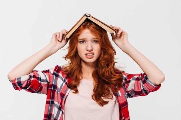 Zmieszana imbirowa kobieta w koszulowej mienie książce na jej głowie