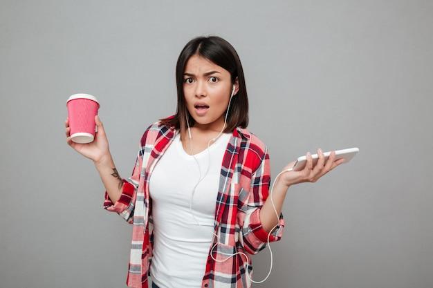 Zmieszana kobieta trzyma filiżankę kawy i słuchającą muzykę.