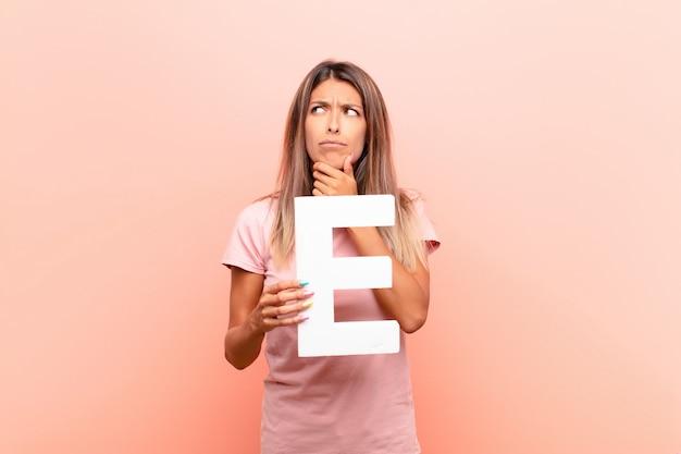 Zmieszana kobieta trzyma literę e abecadło tworzyć słowo