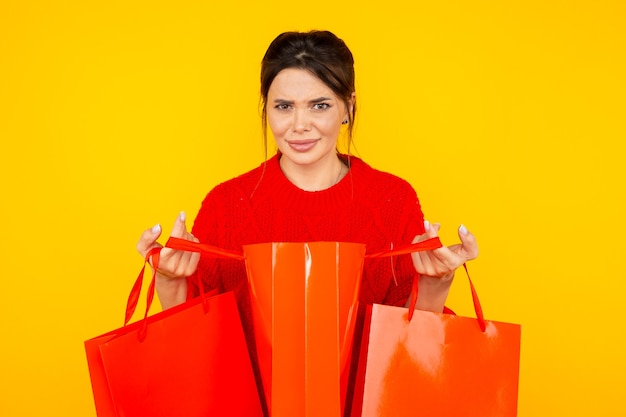 Zmieszana kobieta z czerwonymi torbami na żółto