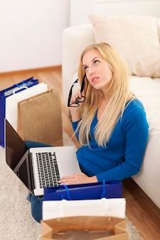 Zmieszana kobieta z laptopem i torbami na zakupy