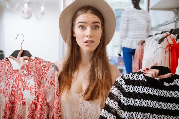 Zmieszana ładna młoda kobieta wybiera sukienkę w sklepie odzieżowym