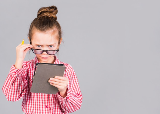 Zmieszana mała dziewczynka w szkłach używać pastylkę
