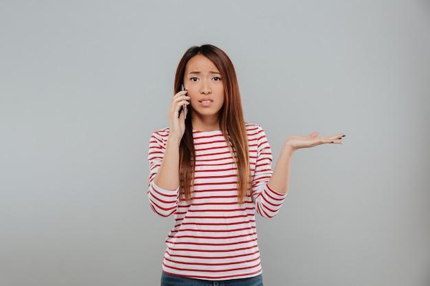 Zmieszana młoda azjatykcia kobieta opowiada telefonem