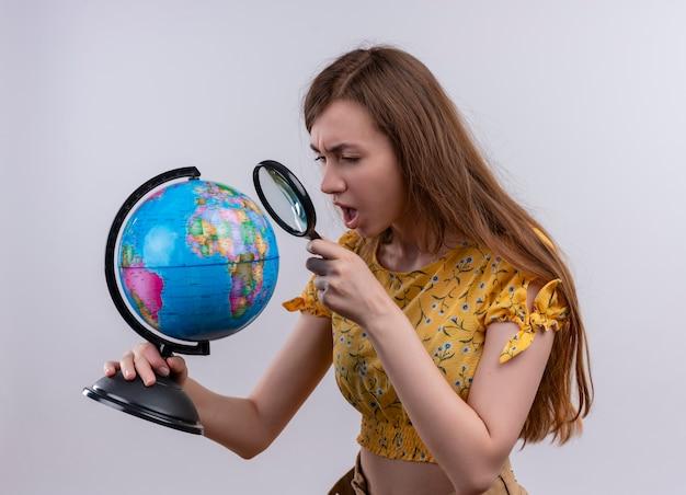 Zmieszana młoda dziewczyna trzyma kulę ziemską i patrząc przez szkło powiększające na odosobnionej białej przestrzeni