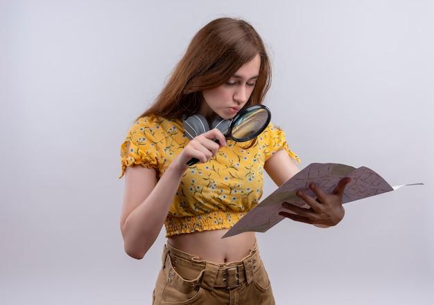 Zmieszana młoda dziewczyna trzyma mapę i patrząc na nią przez szkło powiększające na odosobnionej białej przestrzeni z miejsca na kopię