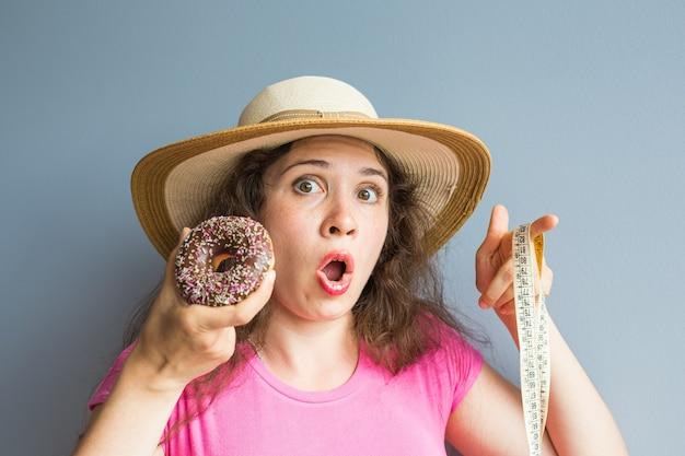 Zmieszana młoda kobieta trzyma pączka i miarkę. pojęcie słodyczy, niezdrowej niezdrowej żywności i otyłości.