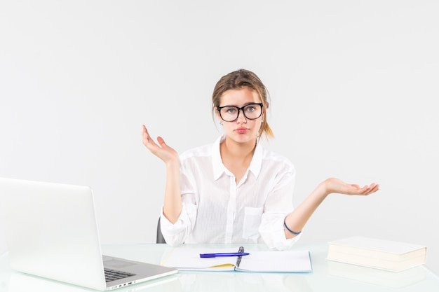 Zmieszana piękna młoda biznesowa kobieta przy biurkiem z laptopem odizolowywającym na białym tle
