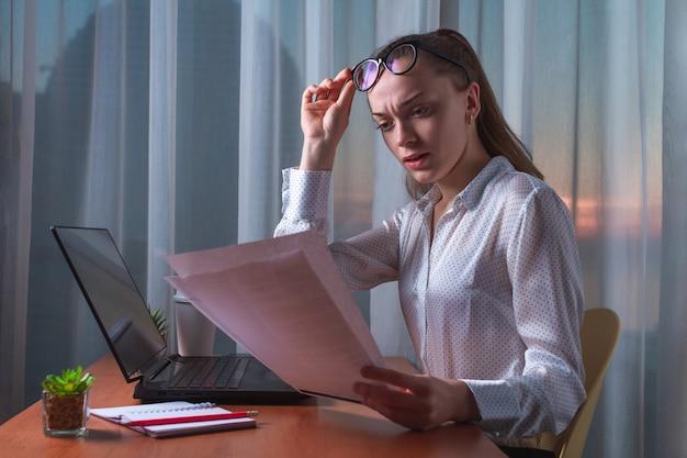 Zmieszana, sfrustrowana kobieta biznesu mająca problem z dokumentami i raportami.