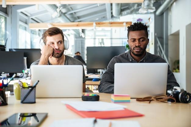 Zmieszani młodzi koledzy siedzi w biurowym coworking