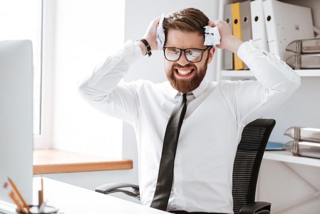 Zmieszany biznesmena obsiadanie w biurze i mieniu tapetujemy