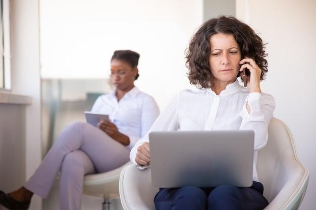 Zmieszany bizneswoman opowiada na telefonie