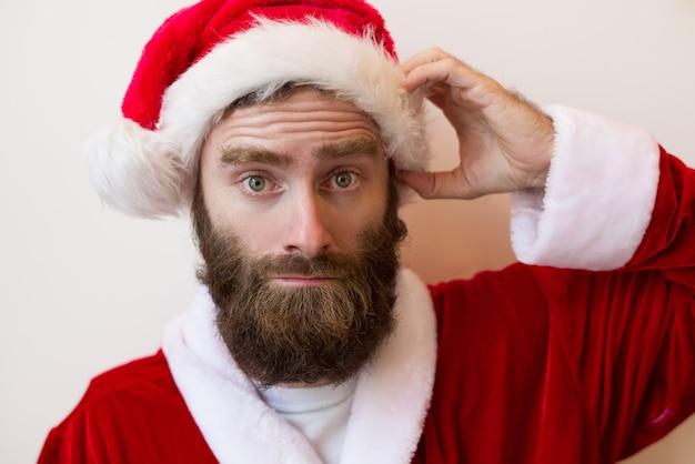 Zmieszany brodaty mężczyzna jest ubranym święty mikołaj kostium
