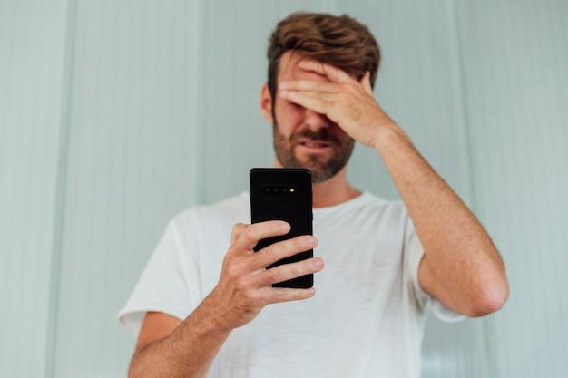 Zmieszany mężczyzna trzyma nowożytnego telefon