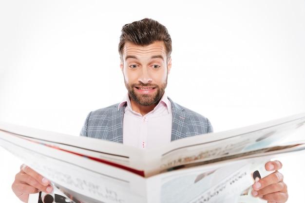 Zmieszany młody człowiek czyta gazette