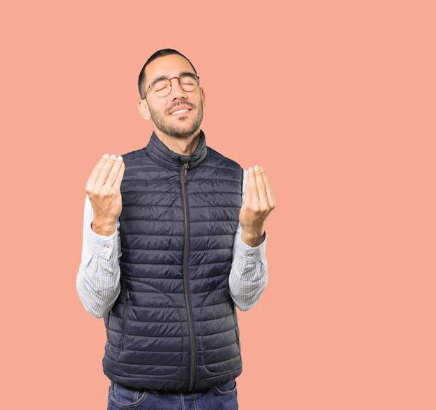 Zmieszany młody człowiek robi włoskiemu gestowi nie rozumie