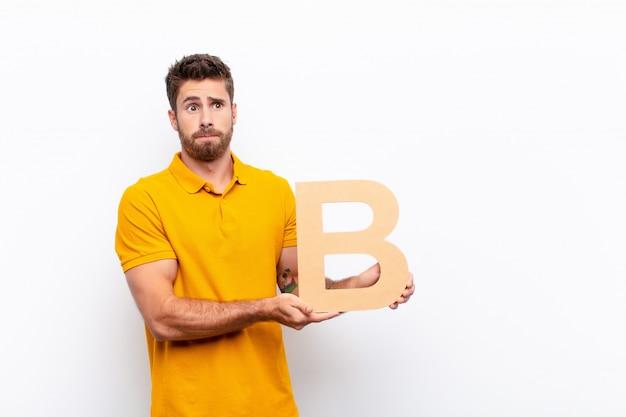 Zmieszany młody człowiek trzyma literę b alfabetu, aby utworzyć słowo lub zdanie